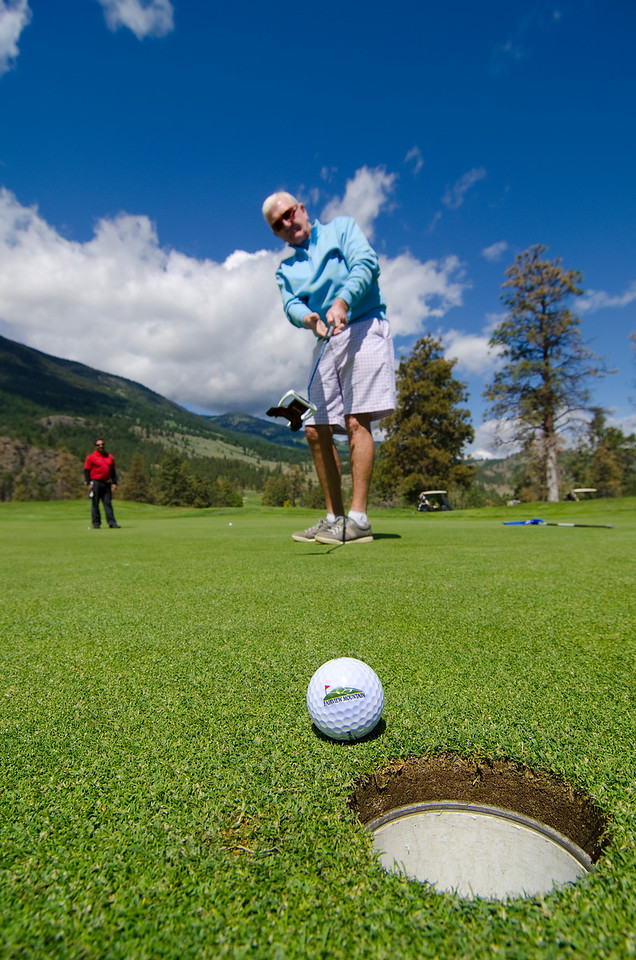 man putting golf ball toward hole