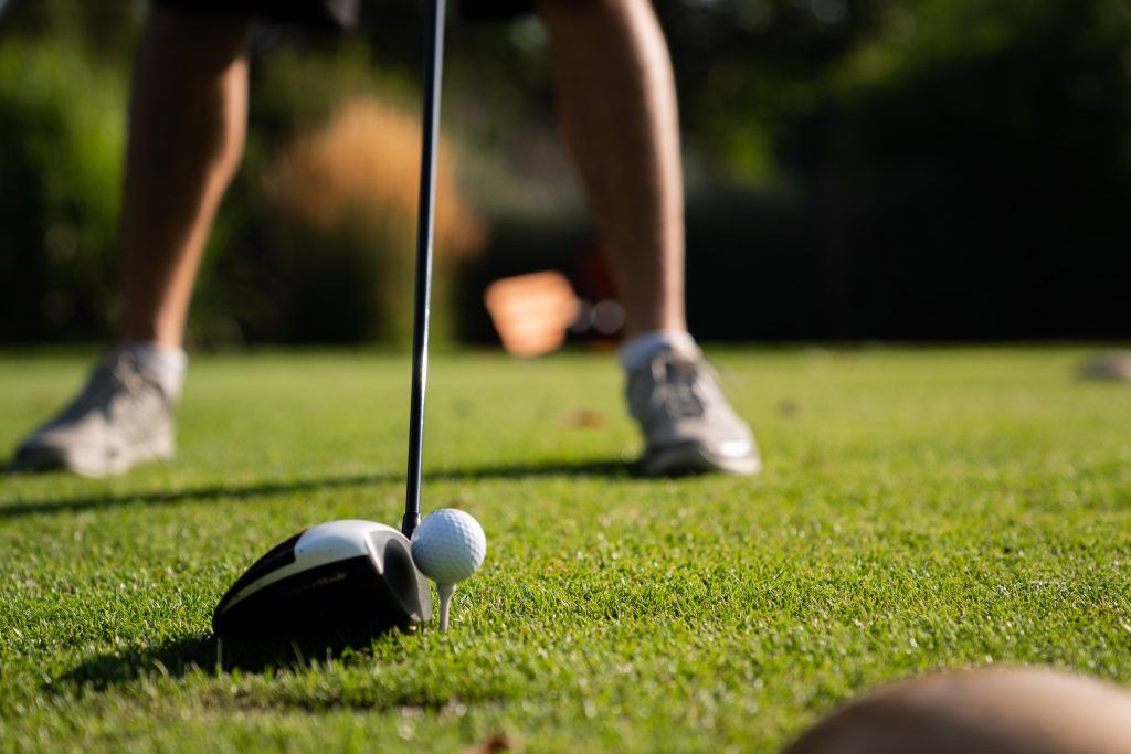 Close up picutre of a golfer lining up tee shot with driver